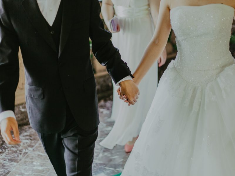 woman-wearing-white-wedding-gown-holding-hands-with-man-1043902